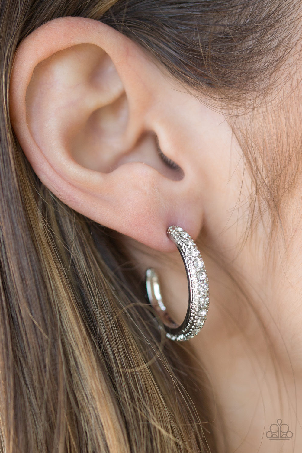 Encrusted in dazzling white rhinestones, a studded silver hoop swings from the ear for a glamorous look. Earring attaches to a standard post fitting. Hoop measures 1