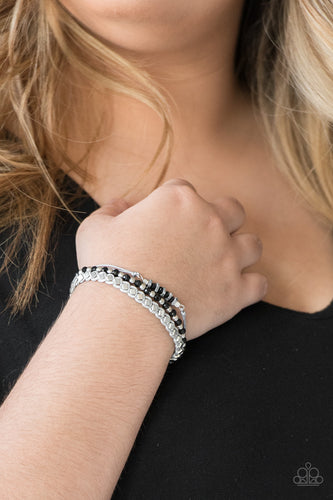 Infused with a strand of faceted black and classic silver beads, shiny gray cording knots around mismatched beads for an edgy look. Features an adjustable sliding knot closure.  Sold as one individual bracelet.  Always nickel and lead free.