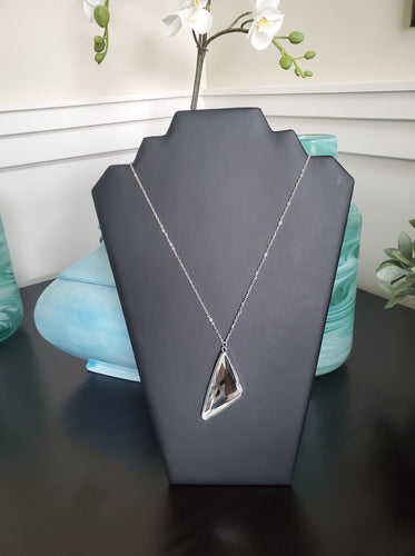 Cut into a striking triangular shape, a faceted white gem swings from the bottom of a lengthened silver chain for an edgy-glamorous fashion. Features an adjustable clasp closure.  Sold as one individual necklace. Includes one pair of matching earrings.  Always nickel and lead free.  August 2020 Fashion Fix Exclusive