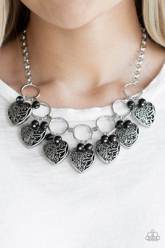 Infused with shiny black beads, vintage locket-like heart frames swing from the bottoms of bold silver hoops, creating a flirtatious fringe below the collar. Features an adjustable clasp closure.  Sold as one individual necklace. Includes one pair of matching earrings.  Always nickel and lead free.