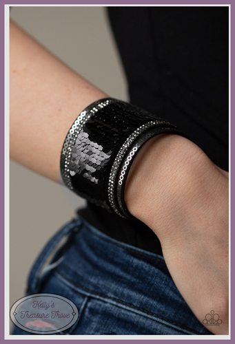 Infused with strands of smoky hematite rhinestones and dainty metallic accents, row after row of shimmery sequins are stitched across the front of a spliced black suede band. Bracelet features reversible sequins that change from black to silver.