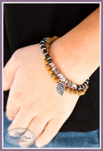 Load image into Gallery viewer, A collection of earthy wooden beads, dainty silver accents, and faceted black beads are threaded along a lengthened stretchy band. Infused with a silver leaf charm, the stretchy band double-wraps around the wrist for a layered look.