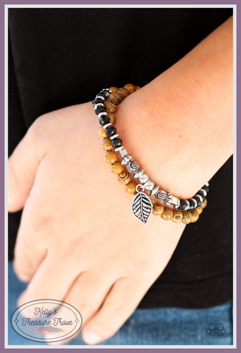 A collection of earthy wooden beads, dainty silver accents, and faceted black beads are threaded along a lengthened stretchy band. Infused with a silver leaf charm, the stretchy band double-wraps around the wrist for a layered look.