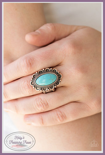 A smooth turquoise stone is pressed into the center of a copper floral frame radiating with antiqued textures.
