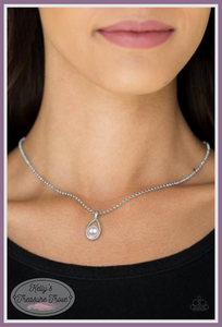 A dainty white pearl dots the bottom of a subtlety twisting silver teardrop frame, creating a classic pendant below the collar. Features an adjustable clasp closure.  Sold as one individual necklace. Includes one pair of matching earrings.  By Paparazzi Accessories.  Always nickel and lead free.