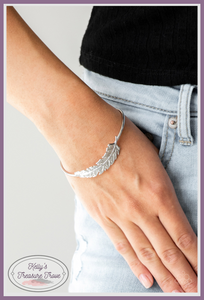 Featuring life-like detail, a shimmery silver feather folds along a dainty silver cuff for a seasonal look.