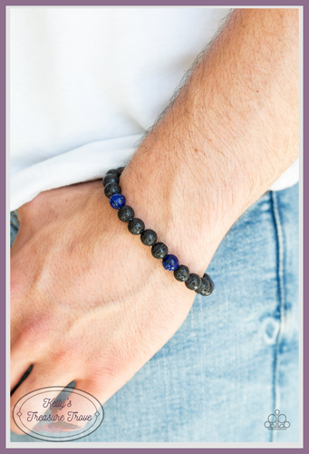 An earthy collection of black lava stones and glassy blue stones are threaded along a stretchy band around the wrist for a seasonal look.
