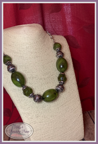 Featuring an array of antiqued silver beads, an icy collection of oversized glassy green beads are threaded along an invisible wire below the collar for a colorful, statement making look.