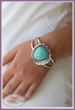Load image into Gallery viewer, Chiseled into a tranquil teardrop shape, a refreshing turquoise stone is pressed into the center of a layered silver cuff. Stamped in tribal inspired patterns, mismatched silver frames and an antiqued silver feather wraps around the stone center for a seasonal flair.