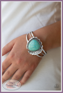Chiseled into a tranquil teardrop shape, a refreshing turquoise stone is pressed into the center of a layered silver cuff. Stamped in tribal inspired patterns, mismatched silver frames and an antiqued silver feather wraps around the stone center for a seasonal flair.
