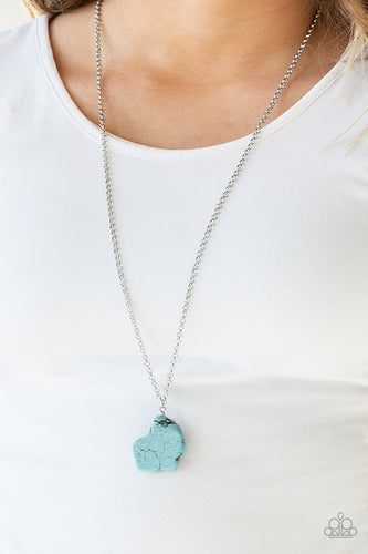 A large turquoise stone pendant hangs from a wire-wrap fitting for an artisan flair. Infused with an elongated silver chain, the earthy stone features rigid and uneven edges as if the pendant had been chipped from a cliff. As the stone elements in this piece are natural, some color variation is normal. Features an adjustable clasp closure.  Sold as one individual necklace. Includes one pair of matching earrings.  Always nickel and lead free.