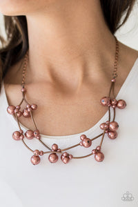 Cylindrical copper beads and clusters of pearly copper beads are threaded along invisible wires, creating bubbly layers below the collar for a refined look. Features an adjustable clasp closure.  Sold as one individual necklace. Includes one pair of matching earrings. Always nickel and lead free.