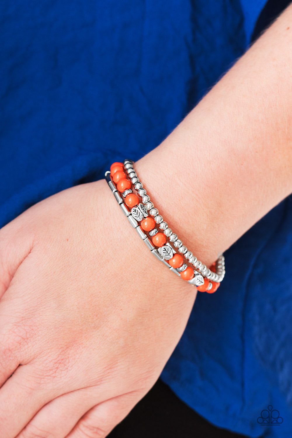 Vivacious orange beads and silver beads featuring round and cylindrical shapes are threaded along elastic stretchy bands. Stamped in tree-like patterns, faceted silver beads are sprinkled between the colorful beads for a whimsical finish.  Sold as one set of three bracelets.  Always nickel and lead free.
