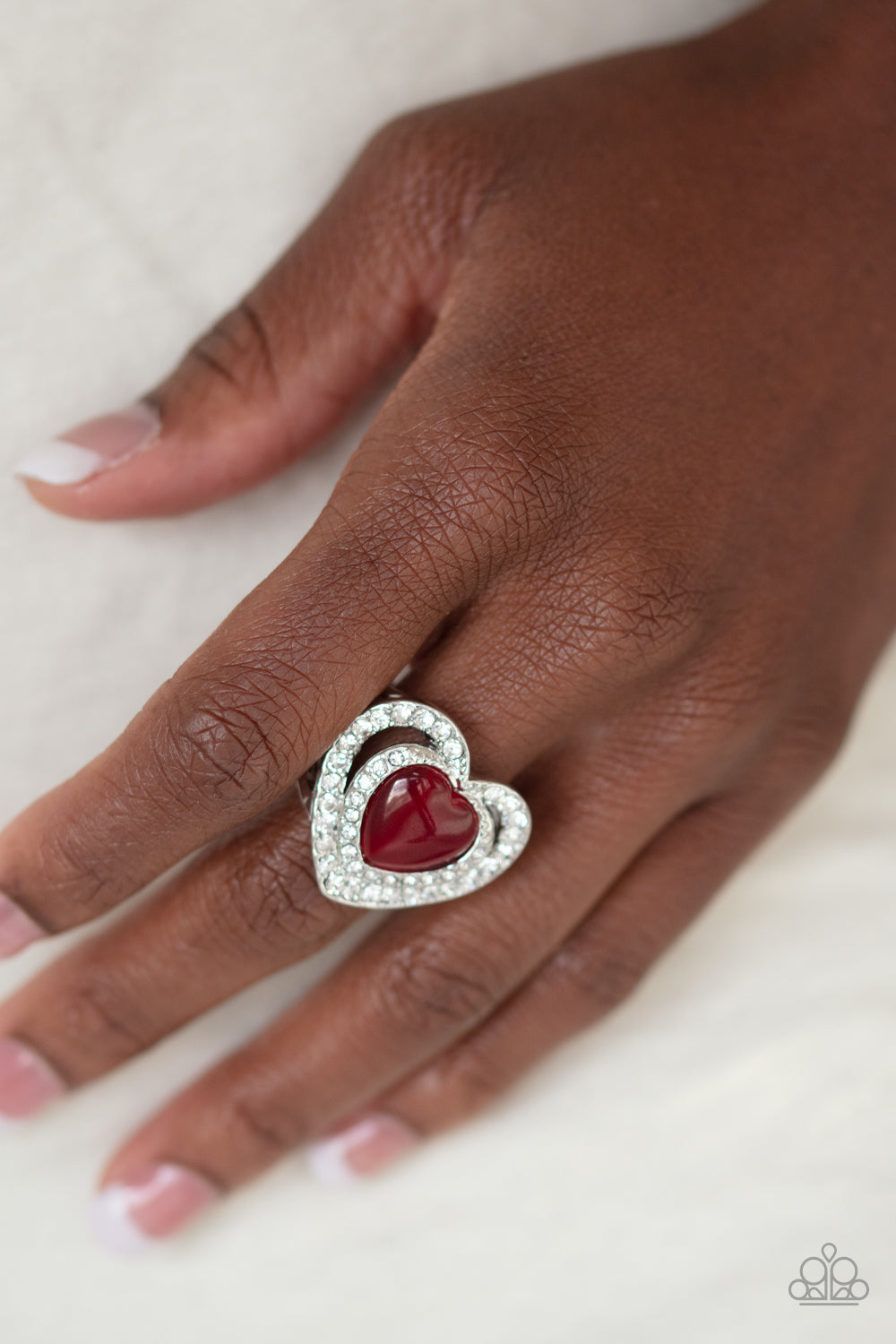 Encrusted in glittery red rhinestones, silver ribbons crisscross across the finger, creating a dainty band. A glistening silver heart adorns the center of the band for a romantic finish. Features a dainty stretchy band for a flexible fit.  Sold as one individual ring.  Always nickel and lead free.