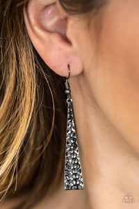 Hammered in endless shimmer, a triangular gunmetal plate swings from the ear in a fierce fashion. Earring attaches to a standard fishhook fitting.  Sold as one pair of earrings. Always nickel and lead free.