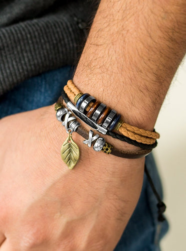 Mismatched strands of leather cording layer across the wrist. Infused with wooden and metallic accents, a shimmery brass leaf charm swings from the wrist for a whimsical finish. Features an adjustable sliding knot closure.  Sold as one individual bracelet.  Always nickel and lead free.