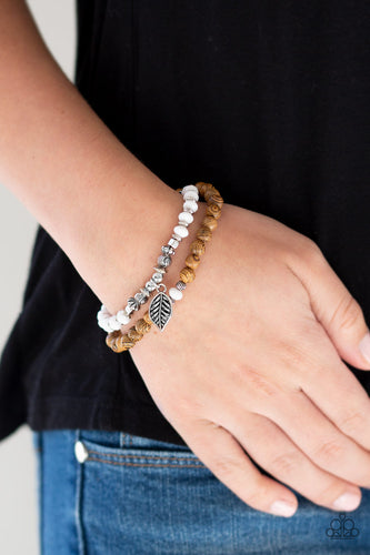 A collection of earthy wooden beads, dainty silver accents, and faceted white beads are threaded along a lengthened stretchy band. Infused with a silver leaf charm, the stretchy band double-wraps around the wrist for a layered look.  Sold as one individual bracelet.  Always nickel and lead free.