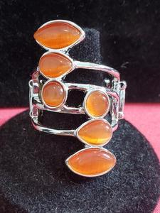 Featuring round, teardrop, and marquise shapes, two frames of glowing orange cat's eye stones stack across a layered silver band for an all around radiance. Features a stretchy band for a flexible fit.  Sold as one individual ring.  Always nickel and lead free.  Fashion Fix Exclusive!
