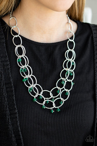 Green crystal-like beads swing from two layers of oversized silver links below the collar for a refined look. Features an adjustable clasp closure.  Sold as one individual necklace. Includes one pair of matching earrings.  Always nickel and lead free.