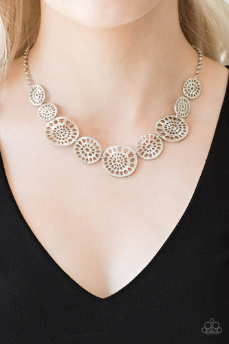 Featuring airy stenciled patterns, shimmery silver discs link below the collar for a whimsical asymmetrical look. Features an adjustable clasp closure.  Sold as one individual necklace. Includes one pair of matching earrings.  Always nickel and lead free.