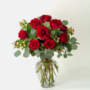 One dozen long-stemmed red roses in a vase with greenery