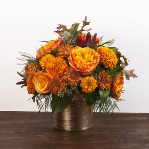 Persephone flower arrangement - fall bouquet of orange, red, and bronze flowers in a gold metallic vase