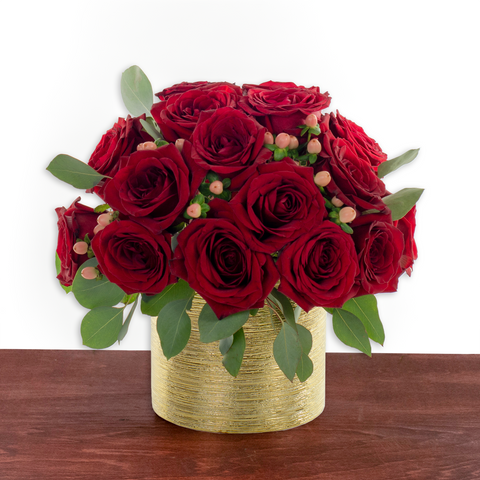 Red roses arranged in a modern gold vase