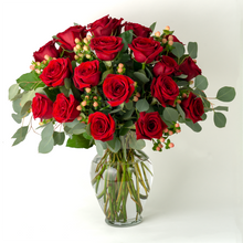 Two dozen long-stemmed red roses in a vase with greenery