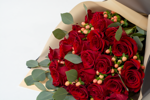 Two dozen long-stemmed red roses arranged in a luxury bouquet