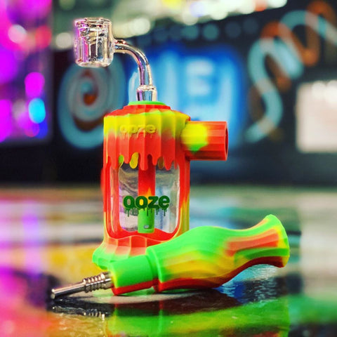 The Ooze Rasta Clobb 4-in-1 Silicone Hybrid device is sitting on a polished floor with the glass banger inserted, and the nectar collector disconnected from the body with the nail inserted.
