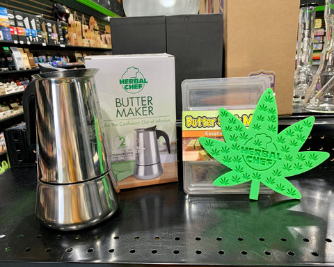 The Herbal Chef Butter Maker, Butter Mold and Potholder are displayed together on a black shelf in the Ooze Wholesale showroom.