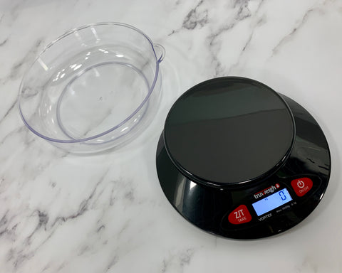 The Truweigh Vortex digital bowl scale is sitting on a white granite counter. The clear weighing bowl is sitting behind the base to the left, which is turned on.