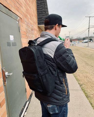 A tall white guy is wearing the Ooze Traveler Backpack outside while lighting up a green Ooze Piper. He has a black and grey winter jacket on and a black flat-brimmed hat.