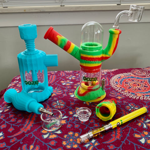 The teal Ooze Clobb, Rasta Cranium, and yellow Slim Twist pen sit together on a table with a maroon patterned tablecloth. The Clobb has the nectar collector out, the cranium has the banger inserted and Armor Bowl sitting to the side for the vape pen.