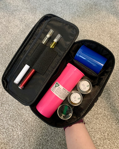 The Ooze Traveler Toiletry Case is being held open to reveal the contents. You can see two Ooze Slim Twist vape pens, a large pink pop top vial, a smaller blue pop top, two wax jars, and a glass dabbing dish