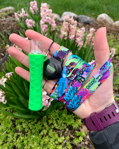The green Ooze Piper 2-in-1 hybrid is shown as a chillum and attached to the Ooze Tag lanyard. It is wrapped around a female hand, and is held above a flower garden with pink hyacinths