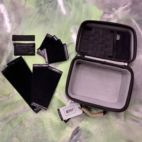 An assortment of Ryot Smell-Proof cases are laid out on a green and gray swirled floor. One larger case has all the inner dividers and accessories spread out on the floor