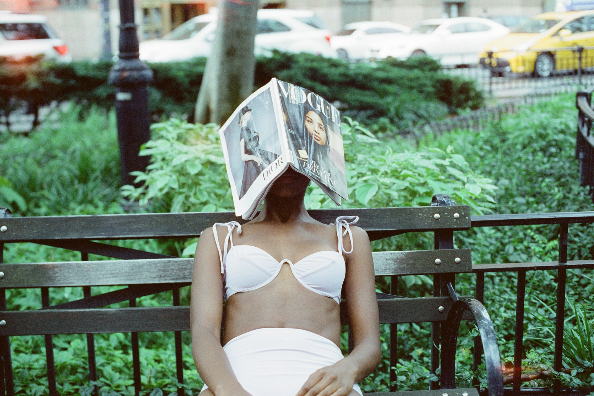 woman sitting on bench with a book on her face