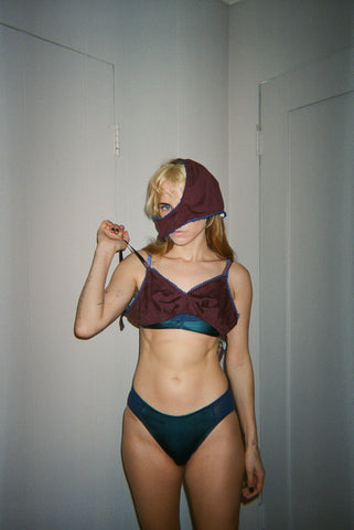 Woman wearing red and blue lingerie with panties on her head.