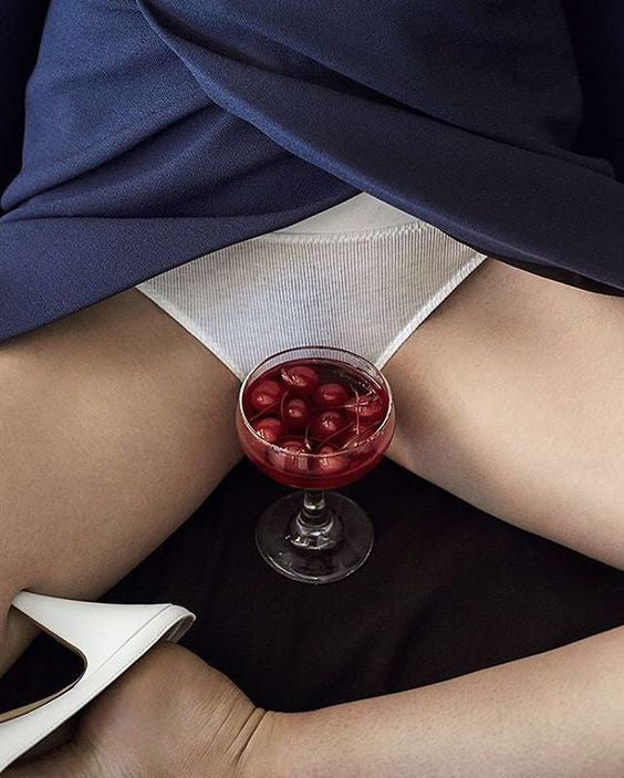 Woman in white panty sitting with glass of cherries