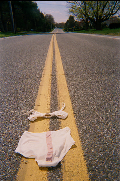 A pink bra and underwear laid in the middle of an empty road.