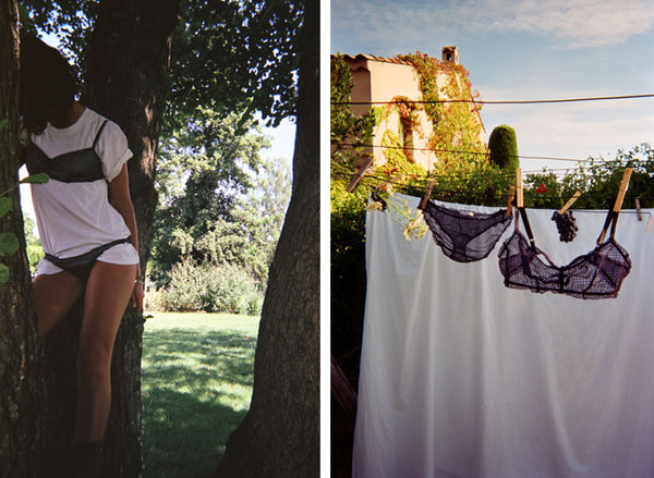 Woman wearing a black bra and underwear over a white T shirt and a black bra and underwear hanging form a clothes line.