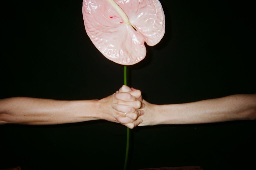 Two hands holding onto a stem with a glass pink flower.