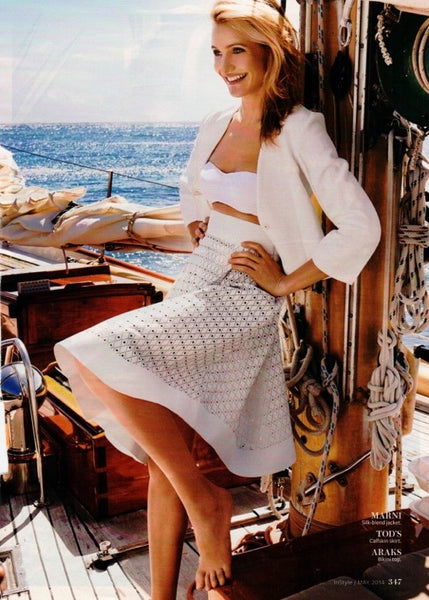 woman standing on boat in white jacket, white bikini top and white skirt