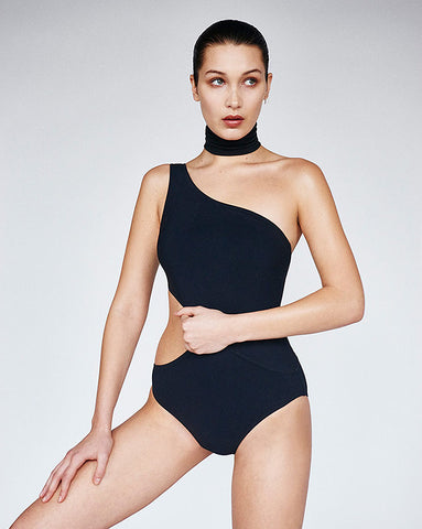 woman standing wearing black one piece