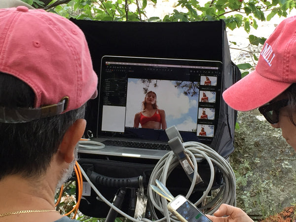 Two photographers in hats editing a photo of a woman in a red bikini top.