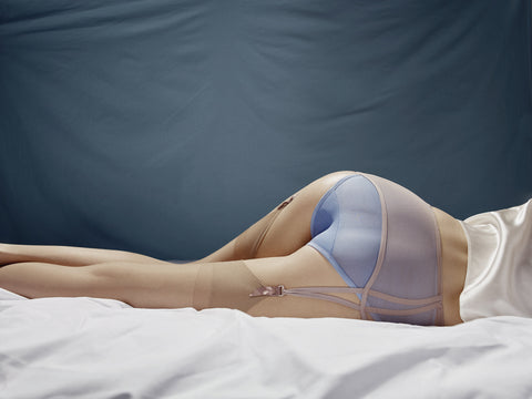 woman laying on bed in blue panty