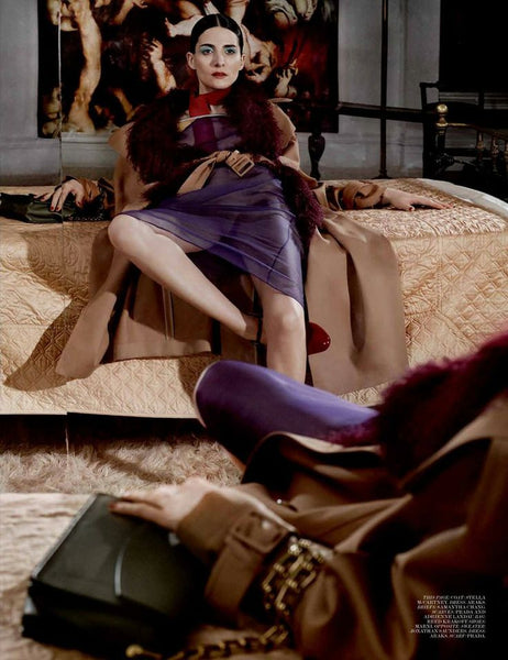Woman laying on bed in purple slip and red and beige jacket