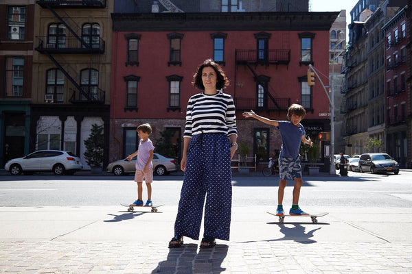 Woman standing in front of an apartment building surrounded by two boys skateboarding.