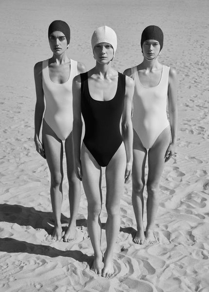 3 women standing, 2 in white one piece, 1 in black one piece